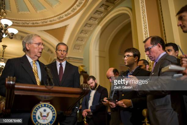 Sen John Thune listens as Senate Majority Leader Mitch McConnell takes questions from reporters during a weekly news conference on Capitol Hill on...