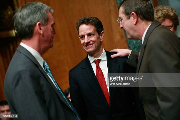 Sen Judd Gregg and Committee Chairman Sen Kent Conrad greets US Treasury Secretary Timothy Geithner before Geithner testified before the Senate...