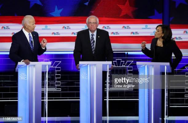 Sen Kamala Harris and former Vice President Joe Biden speak as Sen Bernie Sanders looks on during the second night of the first Democratic...
