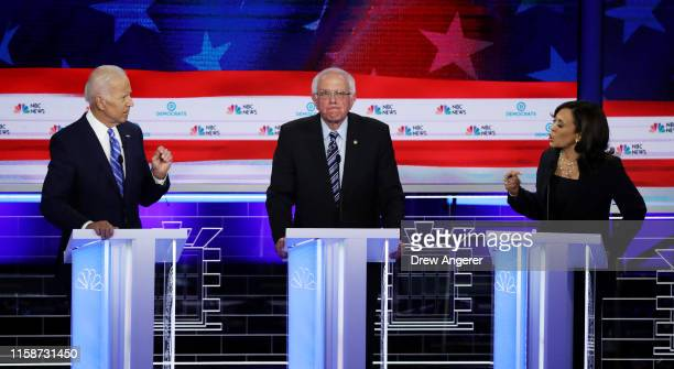 Sen Kamala Harris and former Vice President Joe Biden speak as Sen Bernie Sanders looks on during the second night of the first Democratic...