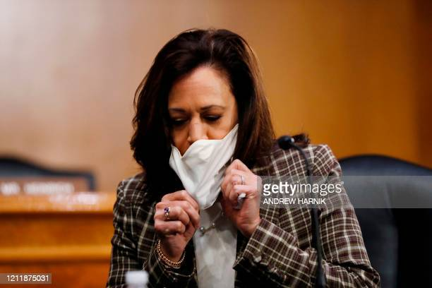 Sen. Kamala Harris, D-CA, removes her face mask as she arrives to a Senate Intelligence Committee nomination hearing for Rep. John Ratcliffe, R-TX,...