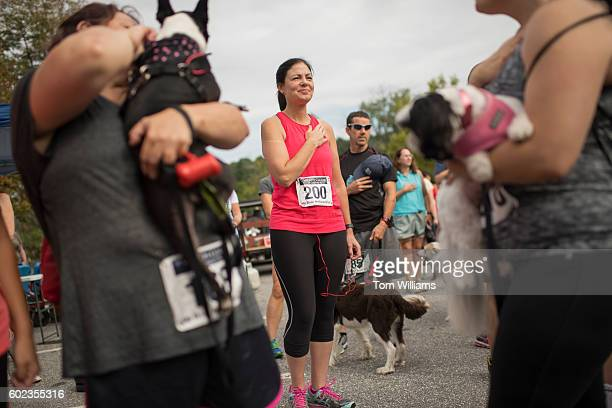 Sen Kelly Ayotte RNH listens to the National Anthem before the My Dogs are Barking 5k race to benefit the Animal Rescue League of NH in Manchester...