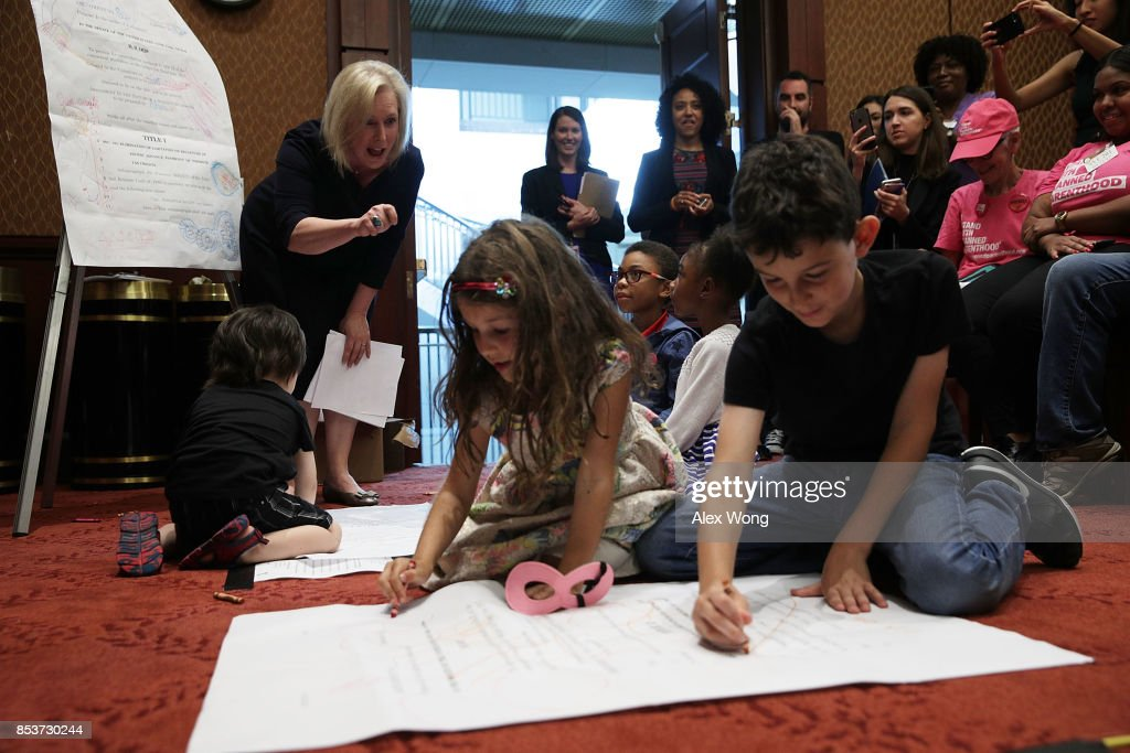U.S. Sen. Kirsten Gillibrand (D-NY) (2nd L) watches children draw on an enlarged page one of the American Health Care Act of 2017 as she arrives at a news conference on health care September 25, 2017 on Capitol Hill in Washington, DC. Activists gathered to urge to reject the Graham-Cassidy health care bill.