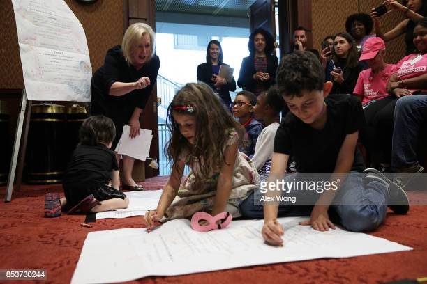 S Sen Kirsten Gillibrand watches children draw on an enlarged page one of the American Health Care Act of 2017 as she arrives at a news conference on...