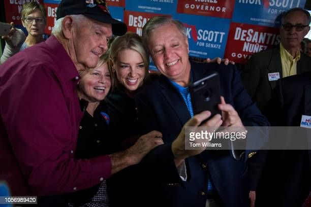 Sen Lindsey Graham RSC right and Florida Attorney General Pam Bondi next to him take a selfie during a rally with Florida governor candidate Rep Ron...