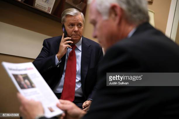 S Sen Lindsey Graham talks on the phone before a news conference to announce opposition to the socalled skinny repeal of Obamacare at the US Capitol...