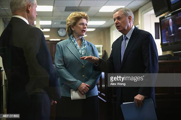 S Sen Lindsey Graham talks to Sen Jeff Sessions as Sen Debbie Stabenow looks on prior to a news conference on currency and trade February 10 2015 on...