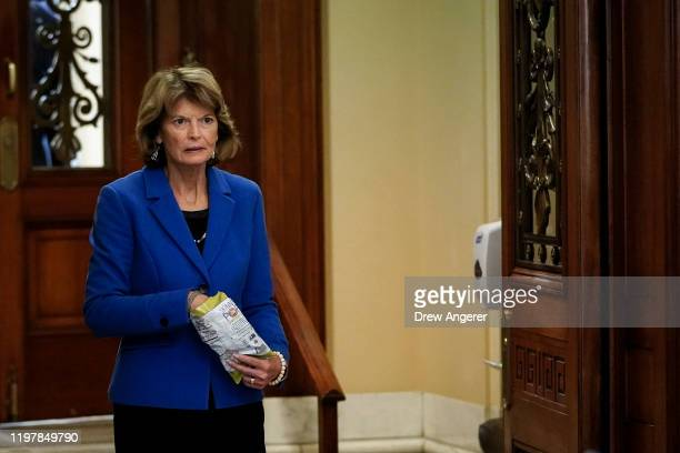 Sen. Lisa Murkowski carries a bag of popcorn as she leaves the Senate chamber during a recess in the Senate impeachment trial of U.S. President...