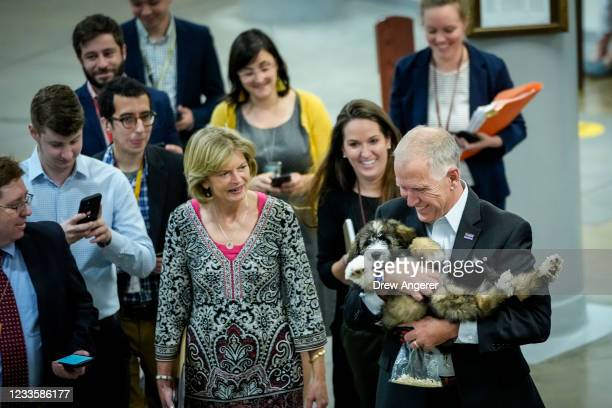 Sen. Lisa Murkowski looks on as Sen. Thom Tillis carries his dog Theo through the Senate subway on his way to a vote at the Capitol on June 21, 2021...