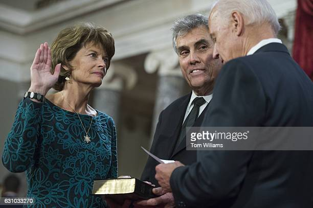 Sen Lisa Murkowski RAlaska is administered an oath by Vice President Joe Biden as her husband Verne Martell looks on during swearingin ceremony in...