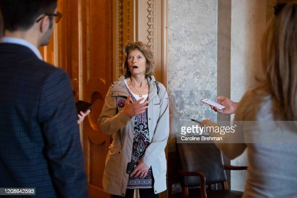 Sen. Lisa Murkowski, R-Alaska, talks to reporters on her way to the Senate floor for a pro forma session in Washington on Monday, March 30, 2020.