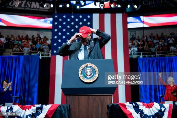 Sen Luther Strange puts on a 'Make America Great Again' cap during his rally with US President Donald Trump at the Von Braun Civic Center September...
