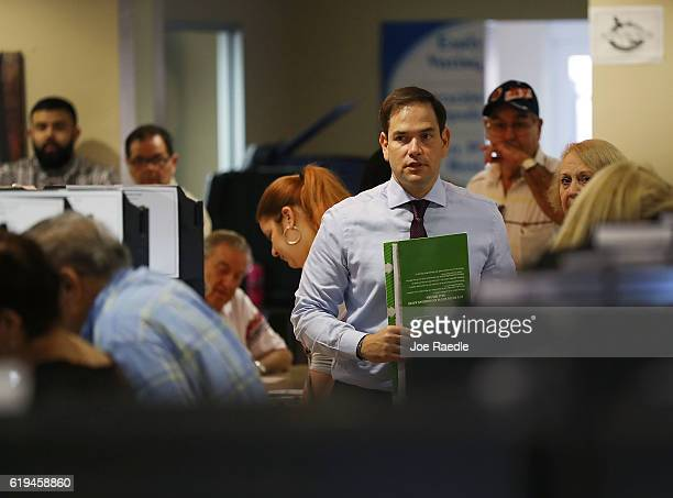 S Sen Marco Rubio carries his ballot to a voting booth as he early votes on October 31 2016 in Miami Florida Mr Rubio is in a race against his...