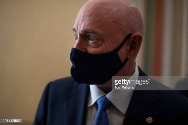 Sen. Mark Kelly, D-Ariz., talks with reporters in the Capitol during a break in the impeachment trial of former President Donald Trump in Washington,...