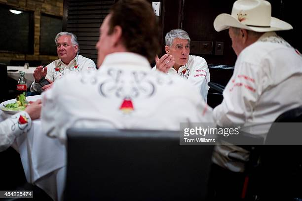 Sen. Mark Udall, D-Colo., second from right, talks with Dean Singleton, right, and others during a Denver Rustlers event in Greenwood Village, Colo.,...