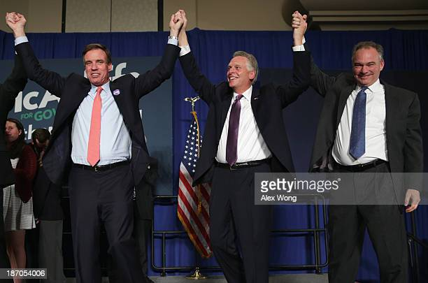 US Sen Mark Warner Democratic Virginia gubernatorial candidate Terry McAuliffe and US Sen Tim Kaine celebrate after McAuliffe has won the race during...