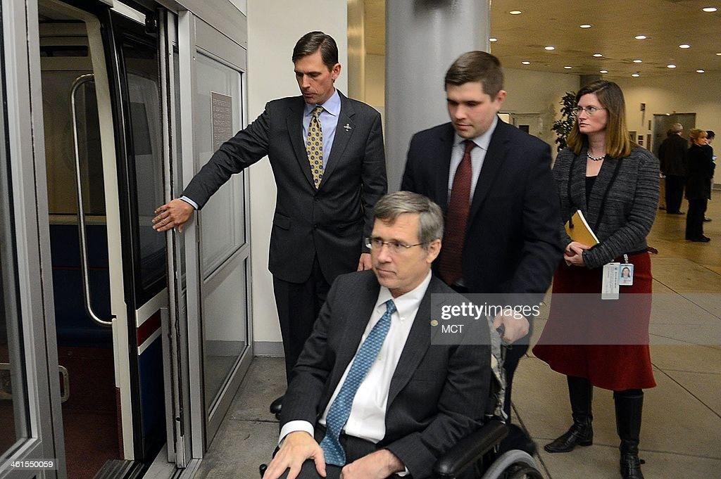 Sen. Martin Heinrich (D-N.M.), the newest member of the U.S. Senate Select Committee on Intelligence, holds the door of the subway open for Senator Mark Kirk from Illinois, while on his way back to his office after voting on the Senate floor on the budget bill on Capitol Hill in Washington, D.C., Dec. 18, 2013.