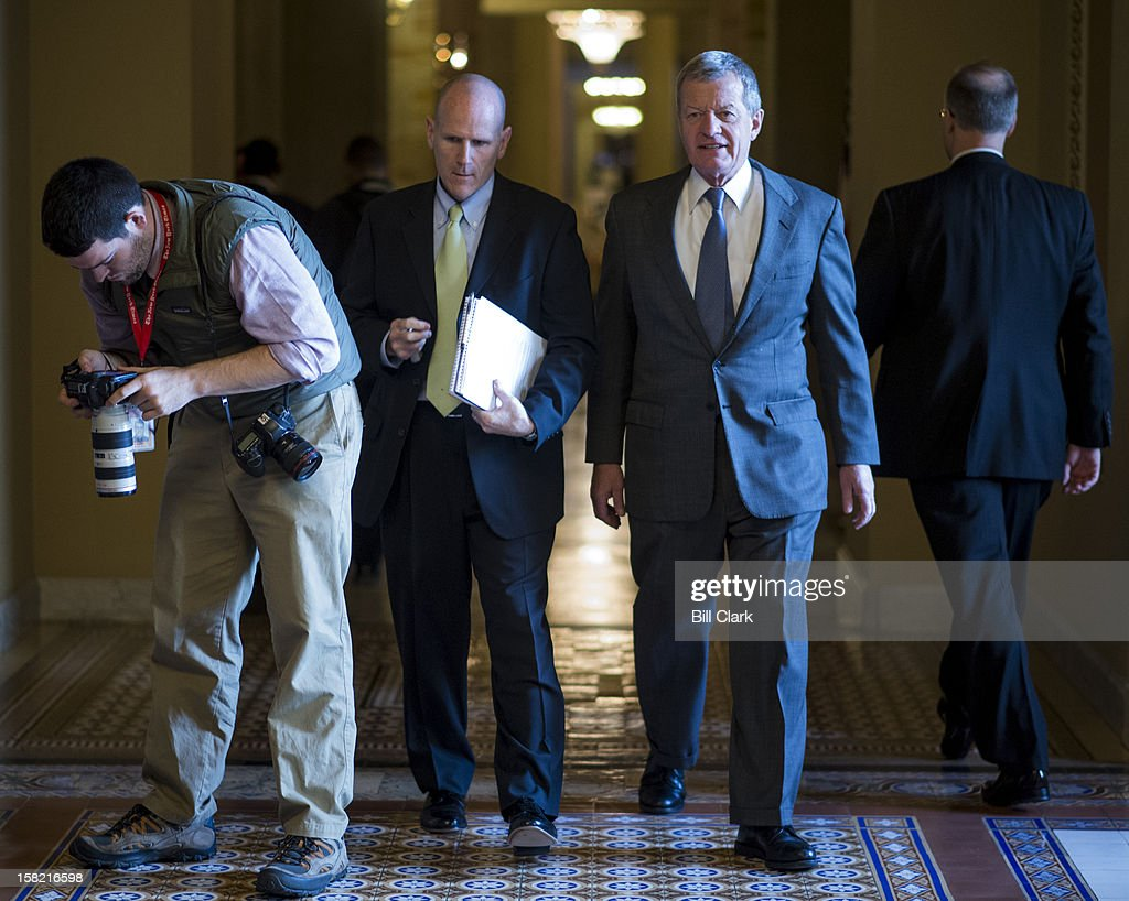 Sen. Max Baucus, D-Mont., right, walks to the Senate floor as a photographer check his camera in the Capitol on Tuesday, Dec. 11, 2012.
