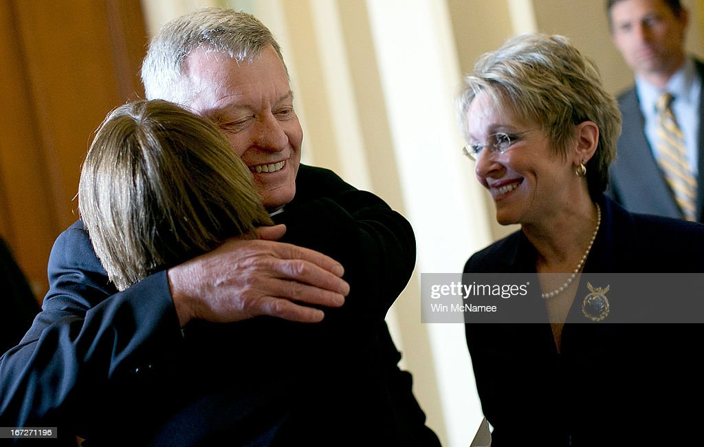 Sen. Max Baucus (D-MT) (C) is hugged by Sen. Amy Klobuchar (D-MN) while walking with his wife Melodee Hanes (R) at the U.S. Capitol April 23, 2013 in Washington, DC. It was announced earlier that Baucus, after 36 years in the Senate, will not seek reelection in 2014.