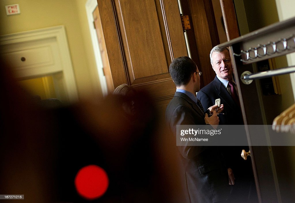 Sen. Max Baucus (D-MT) (R) speaks with a reporter before entering the weekly Democratic policy luncheon April 23, 2013 on Capitol Hill in Washington, DC. It was announced earlier that Baucus, after 36 years in the Senate, will not seek reelection in 2014.