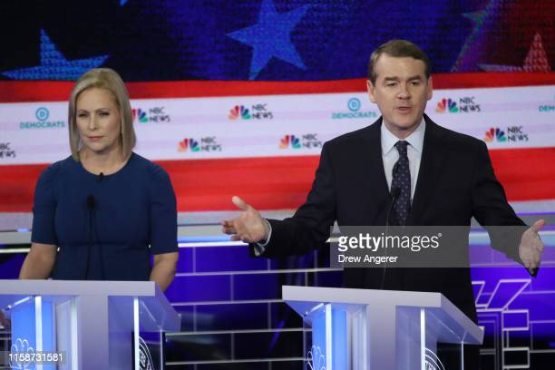 Sen Michael Bennet speaks as Sen Kirsten Gillibrand looks on during the second night of the first Democratic presidential debate on June 27 2019 in...