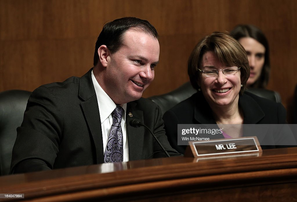 U.S. Sen. Mike Lee (R-UT) and Sen. Amy Klobuchar (D-MN) confer during a hearing of the Senate Judiciary Committee on Capitol Hill March 19, 2013 in Washington, DC. The committee heard testimony on the topic of 'The American Airlines/US Airways Merger: Consolidation, Competition, and Consumers.'