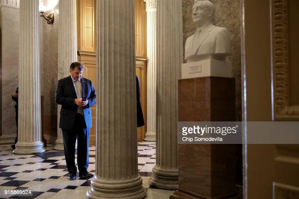 Sen Mike Rounds looks at his phone in the US Captiol following a Republican caucus luncheon February 8 2018 in Washington DC Senate Majority Leader...