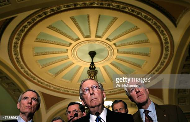 Sen Mitch McConnell answers questions following a weekly policy luncheon at the US Capitol on March 11 2014 in Washington DC Also pictured are Sen...
