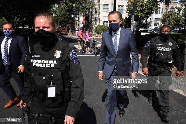 Sen. Mitt Romney is escorted by private security guards as he leaves a meeting of GOP senators at the National Republican Senatorial Committee...