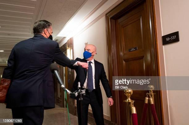 Sen. Mitt Romney, R-Utah, elbow bumps Alejandro Mayorkas, nominee to be Secretary of Homeland Security in the hallway before the start of the...
