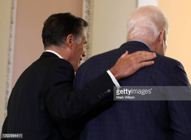 Sen Mitt Romney walks Sen John Cornyn to a GOP caucus meeting after President Donald Trump's impeachment trial ended for the day at the US Capitol on...