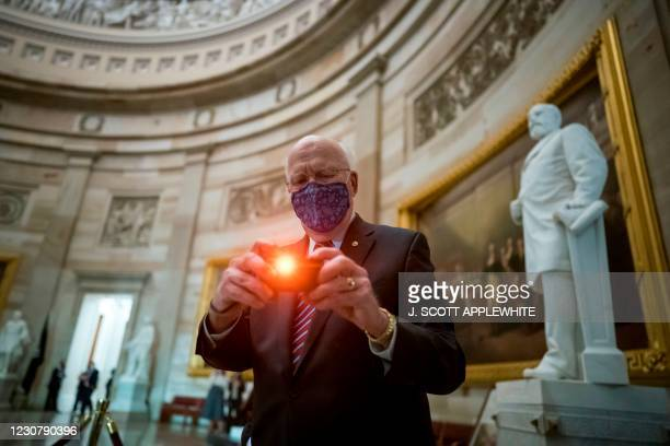 Sen. Patrick Leahy, D-Vt., the president pro tempore of the Senate, pauses to take a snapshot of journalists in the Rotunda of the Capitol awaiting...