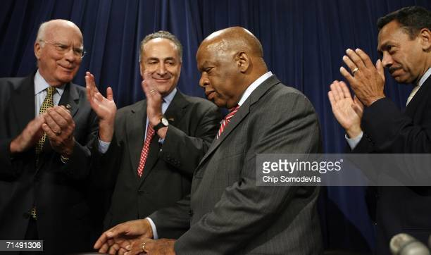 Sen Patrick Leahy Sen Charles Schumer and Rep Mel Watt applaud Rep John Lewis during a press conference at the US Capitol July 20 2006 in Washington...