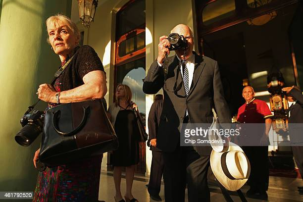S Sen Patrick Leahy takes photographs of journalists assembled outside the Hotel Saratoga after departing the hotel with his wife Marcelle Pomerleau...