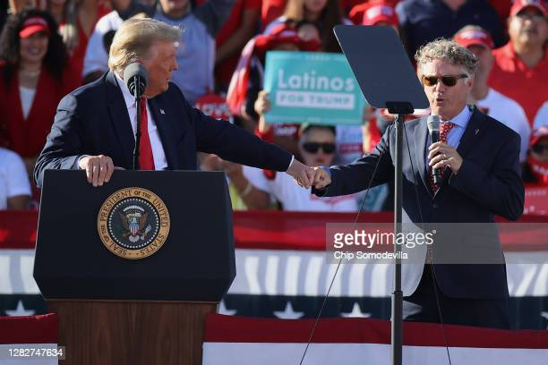 Sen. Rand Paul gives a fist bump to U.S. President Donald Trump while praising the president during a campaign rally at Phoenix Goodyear Airport...