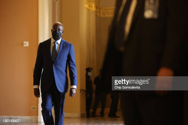 Sen. Raphael Warnock walks to the Senate Chamber on the second day of former President Donald Trump's second impeachment trial at the U.S. Capitol on...