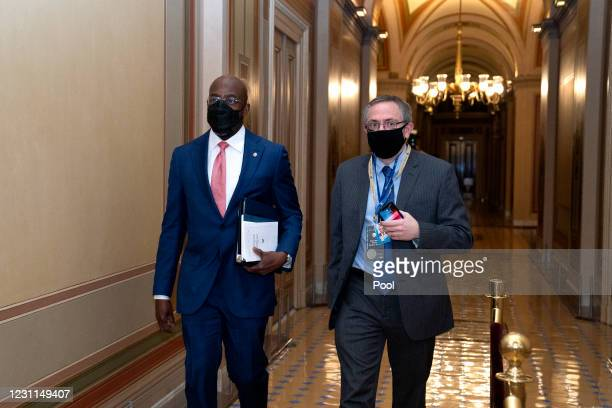 Sen. Raphael Warnock wears a protective mask while walking through the U.S. Capitol on February 13, 2021 in Washington, D.C. Former President Donald...