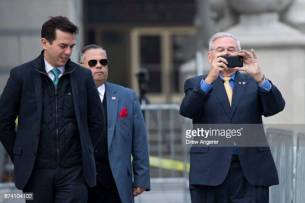 Sen Robert 'Bob' Menendez takes a photo of members of the media as he departs federal court November 14 2017 in Newark New Jersey The jury continues...