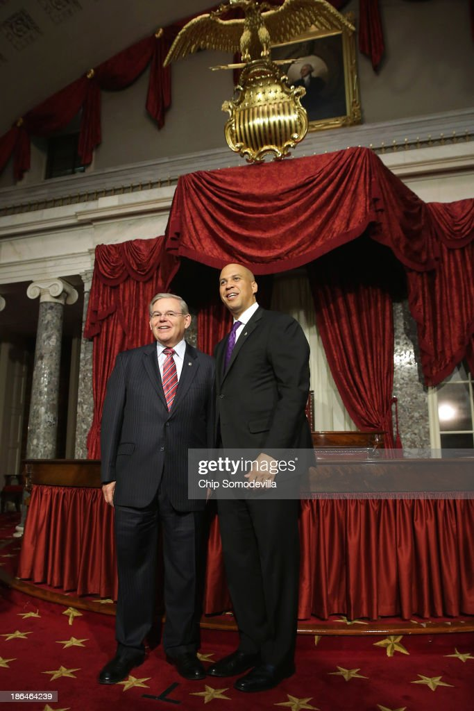 Sen. Robert Menendez (D-NJ) (L) and Sen. Cory Booker (D-NJ) pose for photographs after Booker's ceremonial swearing-in in the Old Senate Chamber at the U.S. Capitol October 31, 2013 in Washington, DC. Booker defeated Republican Steve Lonegan in a special election to replace Frank Lautenberg, who died in June.