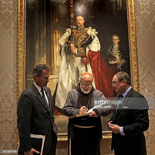 Sen Scott Brown waits to sign the MFA guest book from Cardinal Sean O'Malley as MFA Director Malcolm Rogers holds the book in front of the painting...