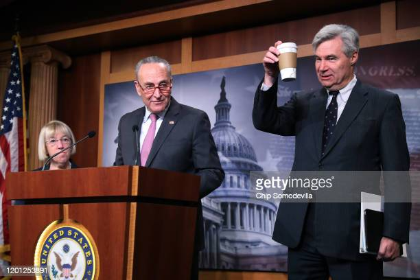 Sen Sheldon Whitehouse holds up a cup of coffee after talking about the previous late night session during a news conference with Senate Minority...