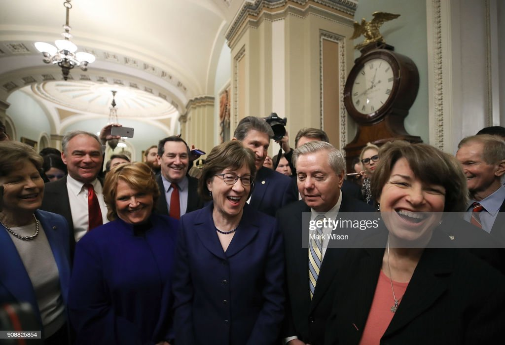 Sen. Susan Collins (R-ME), (C) stands with Sen. Lindsey Graham (R-SC) (2ndR), and other fellow Senators after the Senate voted and passed the CR to reopen the government, at the U.S. Capitol on January 22, 2018 in Washington, DC. Senate leaders reached an arrangement to keep the government open until February 8.