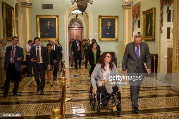 Sen Tammy Duckworth and Senate Minority Leader Chuck Schumer walk to a weekly news conference on Capitol Hill on August 21 2018 in Washington DC