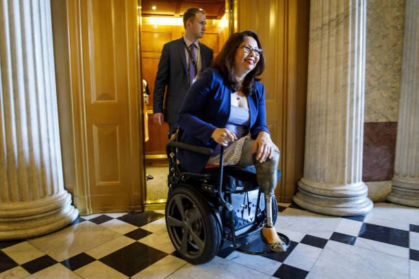 Sen Tammy Duckworth travels with staff between meetings June 20 at the US Capitol