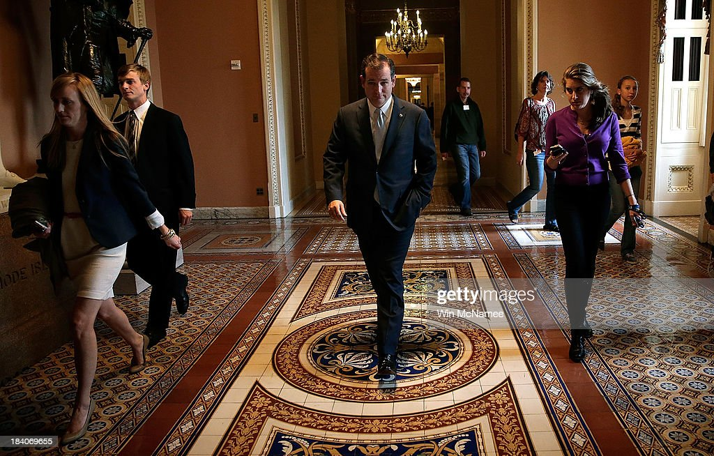 Sen. Ted Cruz (R-TX) (C) walks in the halls of the U.S. Capitol following a meeting at the White House between Republican members of the U.S. Senate with U.S. President Barack Obama on settling the debt limit and government funding issues October 11, 2013 in Washington, DC. The U.S. government shutdown is entering its eleventh day as the U.S. Senate and House of Representatives remain gridlocked on funding the federal government.