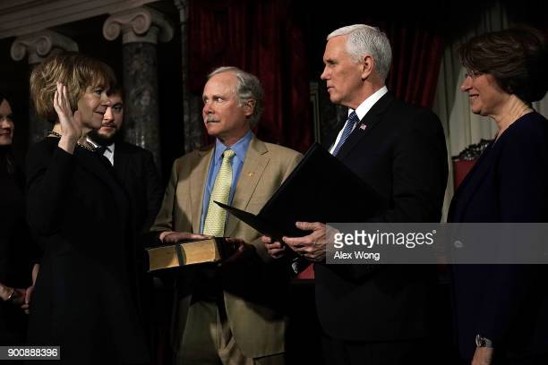 US Sen Tina Smith and her husband Archie Smith participate in a mock swearingin ceremony with Vice President Mike Pence as Sen Amy Klobuchar looks on...