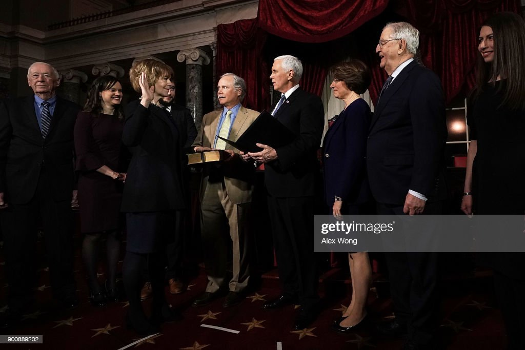 U.S. Sen. Tina Smith (D-MN) (3rd L) and her husband Archie Smith (5th L) participate in a mock swearing-in ceremony with Vice President Mike Pence (6th L) as Sen. Amy Klobuchar (D-MN) (7th L) and former Vice President Walter Mondale (8th L) look on at the Old Senate Chamber of the U.S. Capitol January 3, 2018 in Washington, DC. Smith becomes the junior senator from Minnesota replacing Al Franken following sexual harassment allegations.