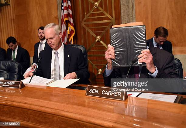 STATES JUNE 9 Sen Tom Carper DDel right covers his face with a binder while chairman Ron Johnson RWisc prepares for the Senate Homeland Security and...