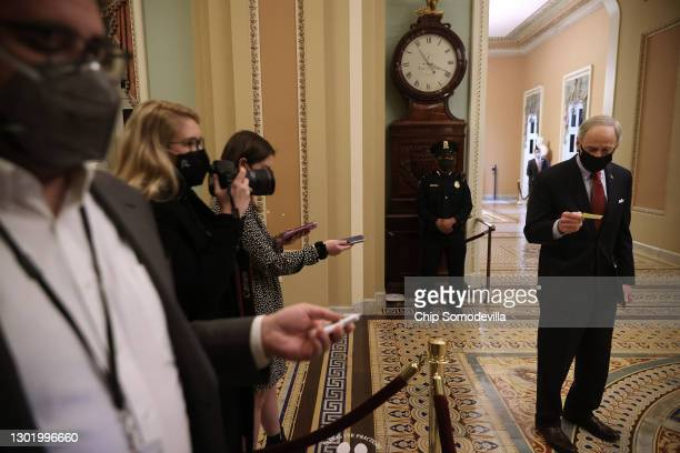 Sen. Tom Carper reads a statement to the gathered reporters outside the Senate Chamber after the conclusion of former President Donald Trump's...