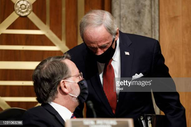 Sen. Tom Carper speaks with Sen. Gary Peters during a Senate Homeland Security and Governmental Affairs Committee confirmation hearing for Neera...